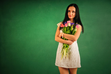 Spring portrait of a woman with tulips on green background