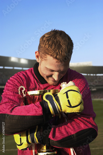 Male goalie triumphantly hugging trophy