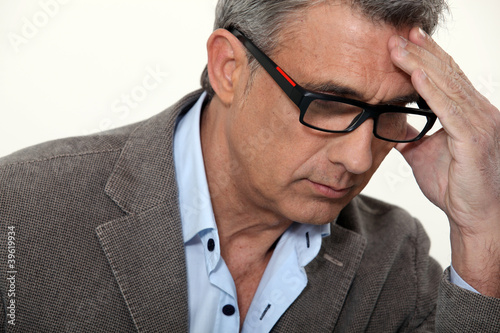 Stressed businessman wearing glasses