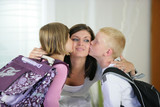 Children kissing their mother