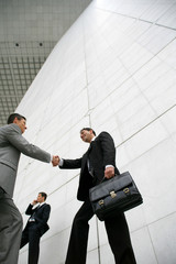 Businessmen handshaking, low-angle shot