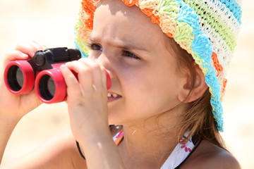 Little girl on the beach with binoculars
