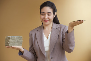 Businesswoman holding uneven stacks of money in both hands