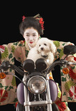 Asian woman in ethnic clothes driving a motorcycle with a dog