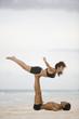 Couple practicing gymnastics on the beach