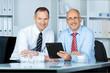 zwei geschäfsleute in einer besprechung mit tablet-pc