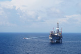 Jack up drilling rig and crew boat in the middle of the sea