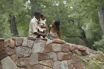 Family standing on a stone bridge