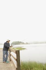 Young man fishing off a pier