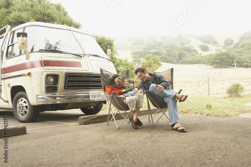Family sitting by truck outdoors