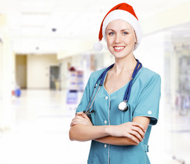 Smiling female medical doctor wearing red hat in a hall of a hos