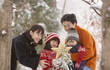 Family with star and snowy tree in forest