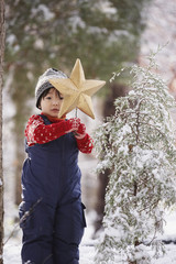 Boy with Christmas star and snowy tree in forest