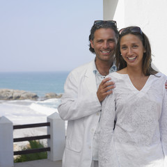 Couple posing on balcony near ocean