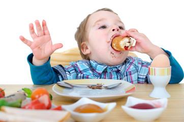 kleiner Junge beim Frühstücksbötchen essen