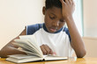 African American boy reading book