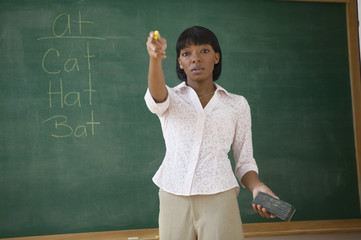 Portrait of female teacher standing by chalkboard and pointing