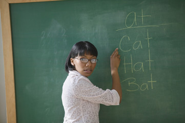 Portrait of female teacher pointing to words on chalk board