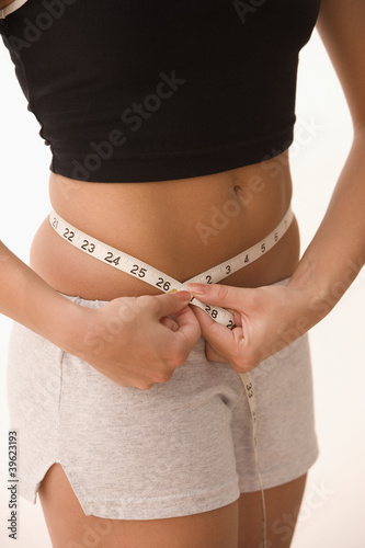 Mid section of girl measuring waist with measuring tape