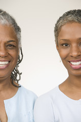 Portrait of mother and daughter standing side by side