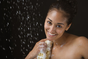 Close up portrait of woman bathing with sponge