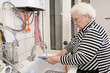 Senior woman washes dishes