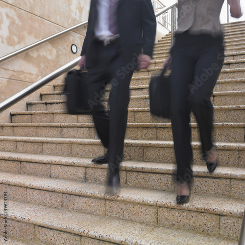 Blurred view of business people's legs descending stairs