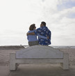 Tourist couple hugging on the beach