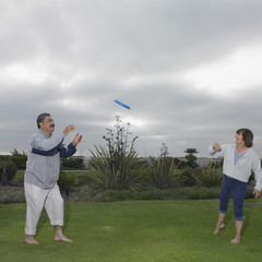 Mature couple playing Frisbee