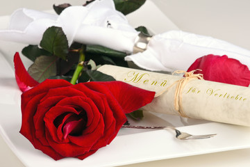 Romantic place setting with red rose and menu-card