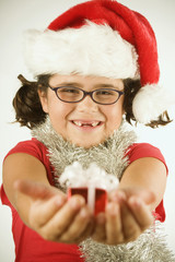 Young girl in a Santa hat holding out a tiny present