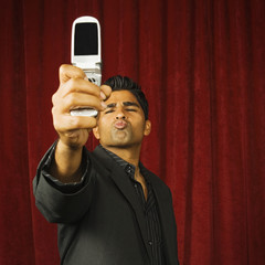 Young man taking a picture of himself with his camera phone