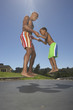 Father and son jumping on a trampoline together
