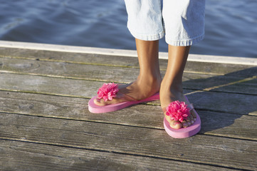Young woman wearing pink daisy flip-flops