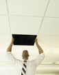 Businessman replacing a ceiling tile