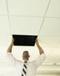 Businessman replacing a ceiling tile