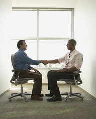 Businessmen shaking hands in swivel chairs