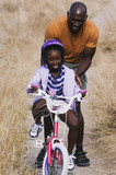 Young man pushing his daughter on her bike