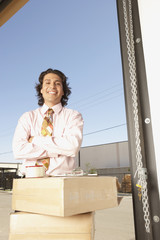 Businessman standing by cardboard boxes in a garage