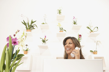 Young woman behind a desk by a wall of flowers