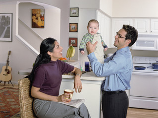 Couple playing with their baby in the kitchen