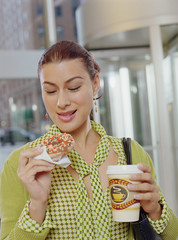 Businesswoman eating a donut