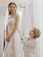 Young bride being fitted in her dress