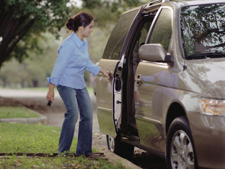 Young woman opening the door of her minivan