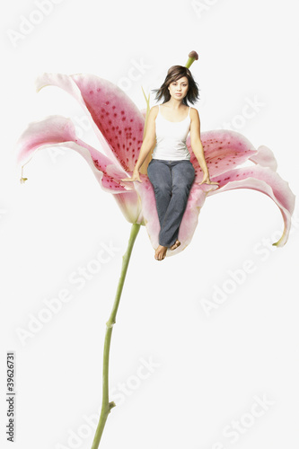 Young woman sitting in a giant flower