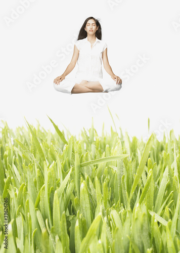Young meditating woman levitating above tall grass
