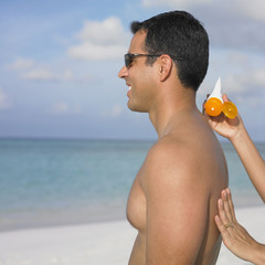 Woman spreading sunscreen on her boyfriend's back