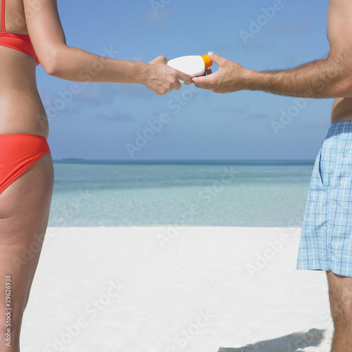 Couple using sunscreen on the beach