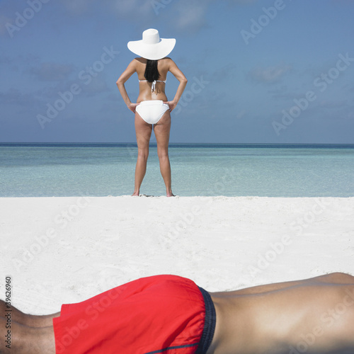 Young woman standing on the beach as boyfriend sunbathes