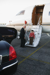 Businessman and young boy on airplane runway